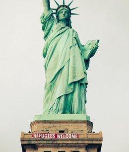 """imagen del contenido """"Bienvenidos refugiados"""", pancarta en la Estatua de la Libertad"""